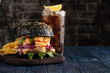 Black burger with fish and shrimps. Fishburger with prawns and French Fries