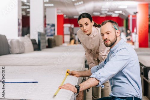 couple measuring mattress with measure tape in furniture store with arranged mattresses