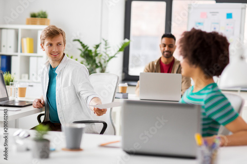 business and people concept - happy creative workers with laptop computers working at office