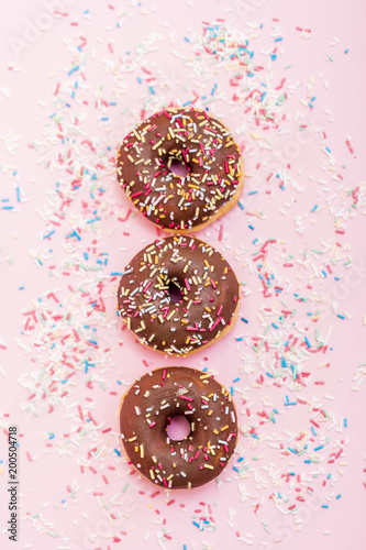 Foto Murales chocolate donuts with colorful sprinkles on pink background