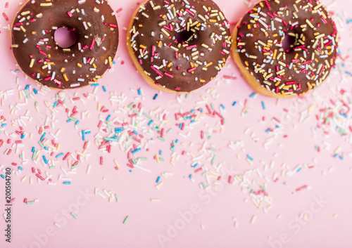 Sticker chocolate donuts with colorful sprinkles on pink background