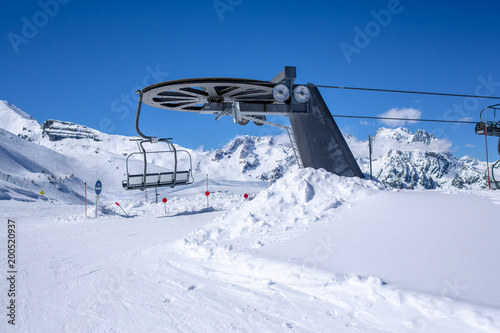 Chair lift at ski resort under blue sky and the sun in France / Winter holidays