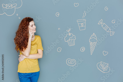 Foto Murales Favorite sweets. Cheerful hungry student feeling optimistic while dreaming about eating delicious sweets