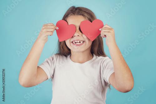 niña sonriente con corazones en los ojos