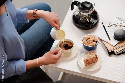 Wall mural cropped shot of woman pouring cream into cup of coffee with cane sugar and piece of cake on coffee table