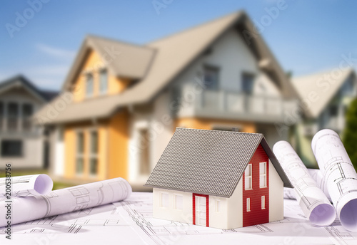 Baupläne mit Architekturmodell und Neubau