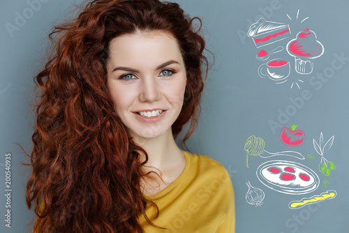 Tasty food. Cheerful young professional chef smiling and thinking about cooking delicious food