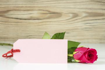 Eine Rose mit Karte vor einem Holz Hintergrund