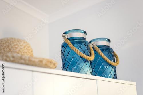 Dwa, niebieskie świeczniki z letnim kapeluszem ładnie zdobiące szafę