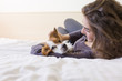 beautiful young woman lying on bed with her cute small dog besides. Home, indoors and lifestyle