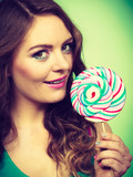 Smiling girl with lollipop candy on green - 200573186