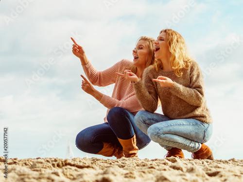 Women on beach having fun pointing