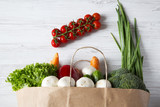 Paper bag of different vegetables on white wooden background. Healthy food. Top view. From above. - 200583722