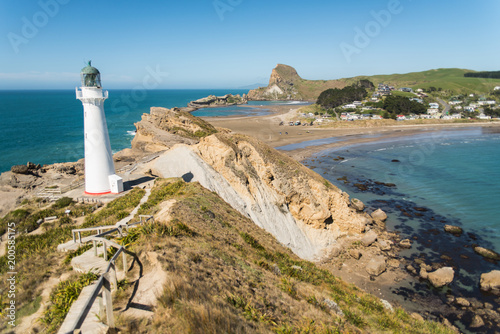 Fotobehang Vuurtoren Landscape view of a lighthouse, ocean, beach, and mountains at Castle Point in New Zealand.