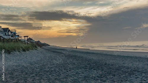 Early Morning time lapse of a beach scene with a beautifully colorful sky - panning from from right to left