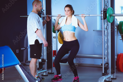 Poster Beautiful woman at the gym exercising with her trainer. Beautiful woman. Gym