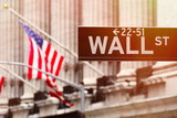 Wall street sign with the New York Stock Exchange on the background