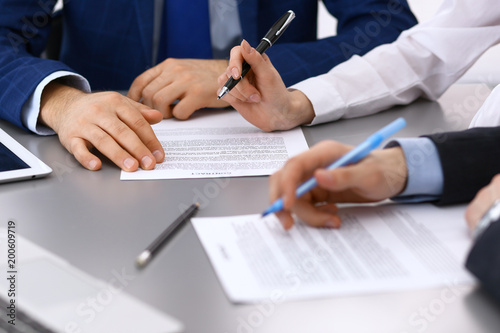 Fridge magnet Group of business people and lawyer discussing contract papers sitting at the table, closeup. Businessman is signing document after agreement done