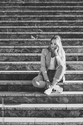 Thoughtful young blonde woman sitting on urban steps.