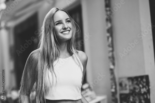 Beautiful young blonde woman smiling in urban background.