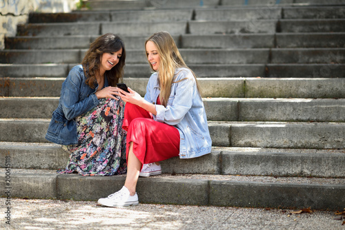 Two young women looking at an smart phone outdoors