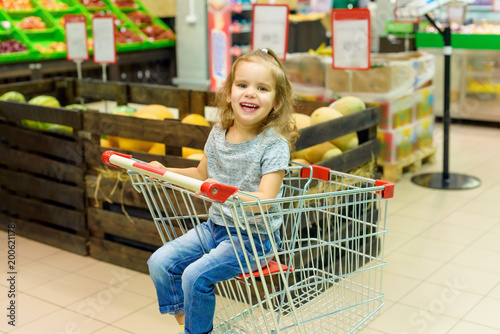 Sale, consumerism and people concept - Happy baby girl sitting in a cart at the supermarket. Child helps his family to shop in the supermarket.