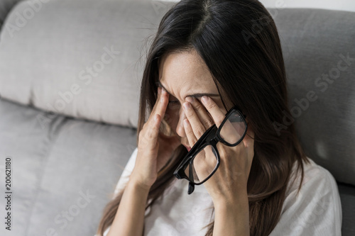 Young woman take off her glasses and siiting on sofa