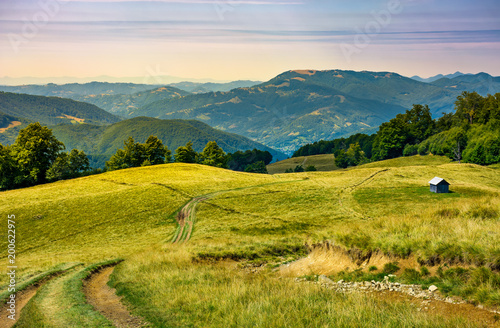 In de dag Honing truck path down the grassy hill. wooden shed on the hillside. beautiful landscape with Krasna mountain ridge in the distance in evening light. Carpathian mountains, Ukraine