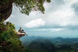 Hiker rest on a cliff,woman enjoy landscape of nature - 200623397
