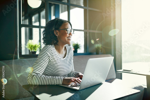 Uśmiechnięta młoda Afrykańska kobieta pracuje online z jej laptopem