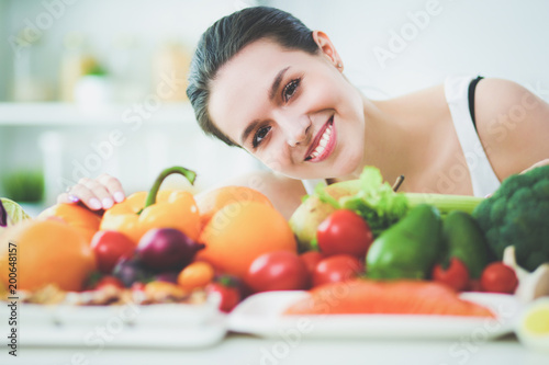 Young and cute woman sitting at the table full of fruits and vegetables in the wooden interior - 200648157