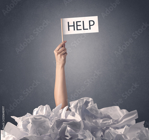 Female hand emerging from crumpled paper pile holding help sign  © ra2 studio
