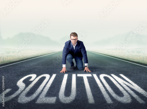 Foto Murales Young determined businessman kneeling before solution text