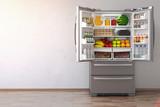 Fototapety Open fridge  refrigerator full of food in the empty kitchen interior.