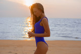 Beautiful girl in a blue bathing suit on a golden beach