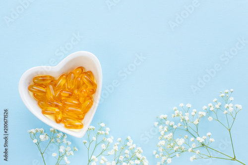Plexiglas Apotheek Health prevention concept, heart-Cup with a bunch of different pills and vitamins and omega, on blue background, top view with gypsophila