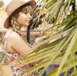 Retrato modelo blanca y rubia, con pelo largo, en una trenza, con pamela, y guantes mirando a traves de una palmera verde.