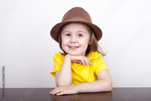 A cute little girl is sitting at a table in a hat