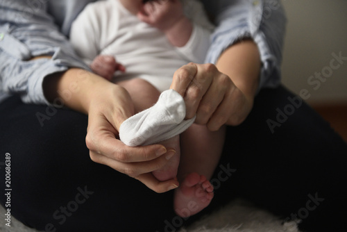 Young mother puts the socks on her little baby