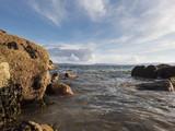 Ocean, rocks, Irish coast, blue cloudy sky over water. The Burren peaks in far background. Galway bay.
