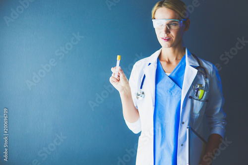 Female medical or research scientist or doctor using looking at a test tube of clear solution in a lab or laboratory.