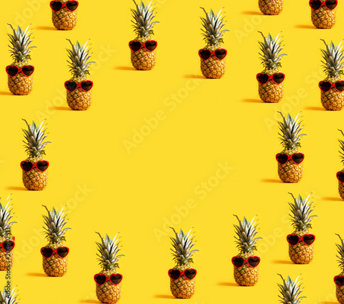 Series of pineapples wearing sunglasses on a yellow background - 200702513