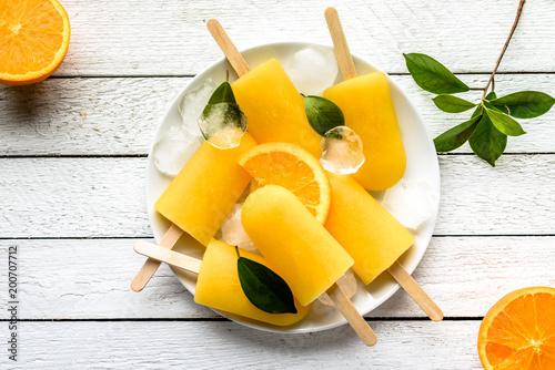 Pomarańczowi popsicles na białym drewnianym tle. Domowe lody wyskakuje, widok z góry płasko świeckich