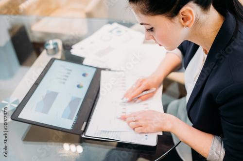 analityk biznesowy studiujący dokumenty z wynikami graficznymi działalności firmy. przetwarzanie informacji i koncepcja analizy danych. młoda kobieta zawodowych w pracy