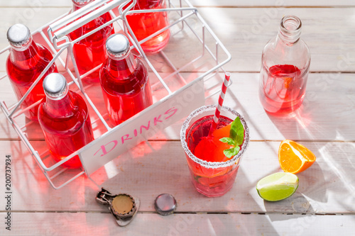 Orangeade in bottle with citrus fruit on white table