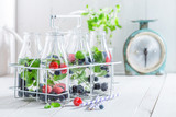 Healthy water in bottle with berries on white table