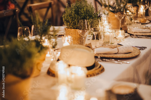 on festive table in wedding banquet area are plates, glasses, candles, cutlery, the table is decorated with compositions of greenery