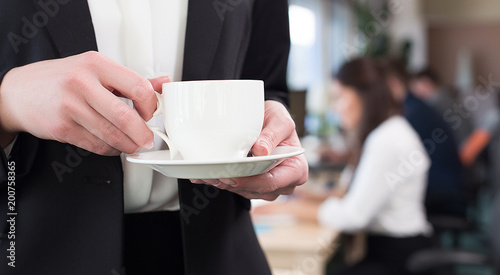 Female adult holding cup of coffee in office during coffee break.