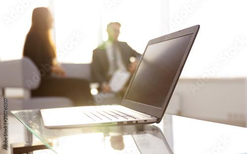 Skoncentruj się na laptopie na stole. Niewyraźne ludzi na tle.