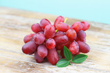 Bunch of red grapes on rustic wooden surface